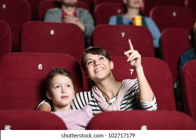 Smiling girl with mother at the cinema
