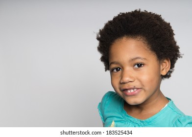 A smiling girl with natural hair.