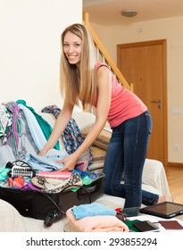 Smiling girl near scattered clothes packing luggage