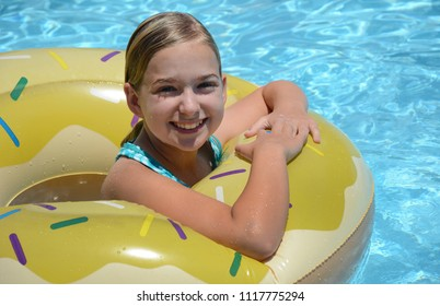 smiling girl on a float in swimming pool