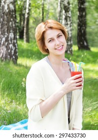 smiling girl on a picnic, drinks juice