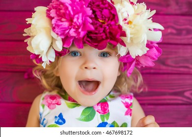 smiling girl on pink background with wreath of peonies on her head