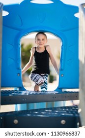 Smiling girl on playground equiment