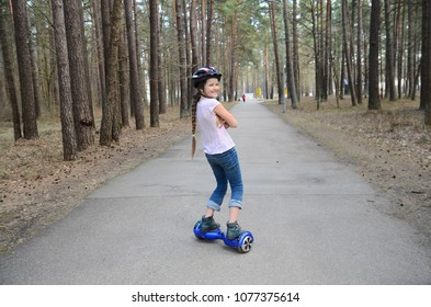 Smiling girl on self-balancing scooter. Kids riding scooter in the park. Balance board for children. Girl learning to ride hoverboard. Modern gadgets for school kid.
