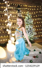 smiling girl in oriental suit dancing at christmas tree