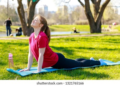 Smiling girl in the park exercise on the yoga mat, Bhujangasana Cobra Pose