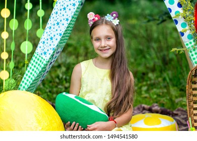 Smiling girl with picnic basket sitting in meadow in a tent