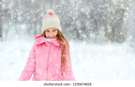 Smiling girl in pink coat in the whirl of snowlakes in winter forest