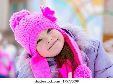 Smiling girl in a pink hat looking up