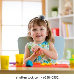 Smiling girl playing with plasticine or play dough at home