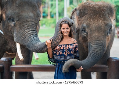 smiling girl posing with two elephants hugging her trunk.