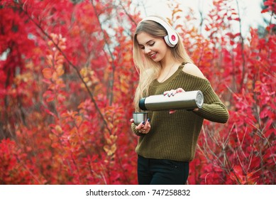 Smiling girl pouring tea from thermos cup, outdoors. Young woman drinking tea at cup. Theme travel. Woman pouring a hot drink in mug from thermos. Girl listen the music in haedphones