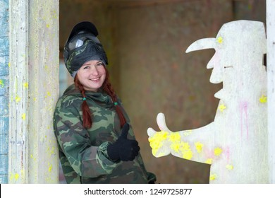 Smiling girl with pretty braids posing on paintball playground