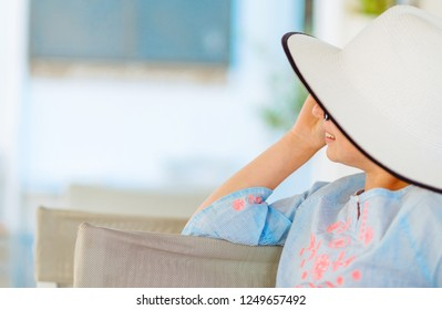 Smiling girl in a pretty white hat and light blue blouse looking away