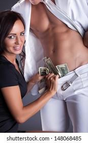 Smiling girl puts dollars in stripper's pants