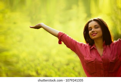 Smiling girl raising arms over outdoor green background with copy space. Freedom and break up concept. Girl pointing up
