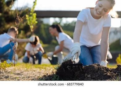 Smiling girl raking up soil for plants