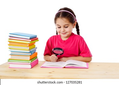 Smiling girl reading the books on the desk with magnifying glass, isolated on white