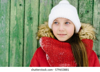 smiling girl in a red jacket and white hat on wooden background green