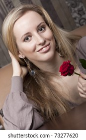 Smiling girl with a red rose
