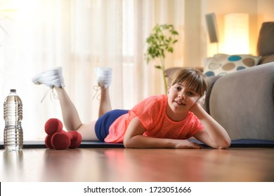 Smiling girl resting on a mat on the floor looking at a camera happy in a sport session in the living room at home.