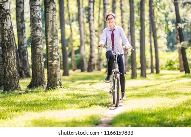 Smiling girl riding a pedal bike passing through a birch forest