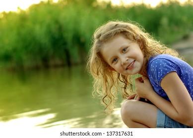Smiling girl in river on sunset light background