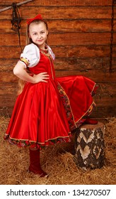 Smiling girl in Russian costume puts her leg on log