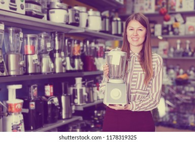 Smiling girl seller offering  blender in domestic appliances section in shop
