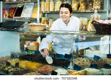 Smiling girl selling candied fruit in a store