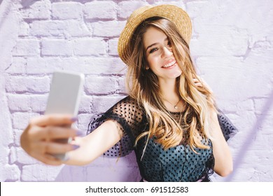 Smiling girl with shiny hair enjoying good weather during walk and making selfie. Outdoor portrait of young laughing woman in romantic outfit taking picture of herself beside white wall.