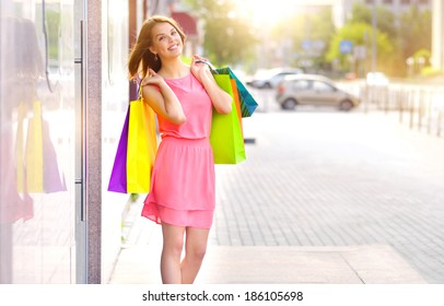 Smiling girl with shopping bags. Background windows
