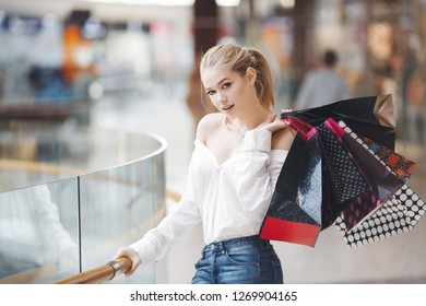 Smiling girl with shopping bags near shopping mall. Young beautiful blonde woman with some shopping bags walking in the street