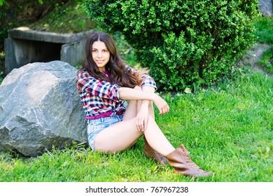 Smiling girl in shorts sitting near a large stone. Horizontal photo