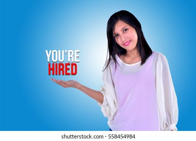 Smiling girl showing open hand palm with text YOU'RE HIRED