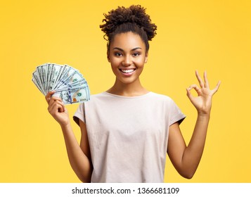 Smiling girl shows money cash and excellent sign, demonstrates that everything is fine. Photo of african american girl wears casual outfit on yellow background. Emotions and pleasant feelings concept.