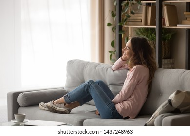 Smiling girl sit on comfortable couch look in window dreaming thinking of future resting in living room, dreamy happy young woman relax on cozy sofa visualizing or imagining spending weekend at home