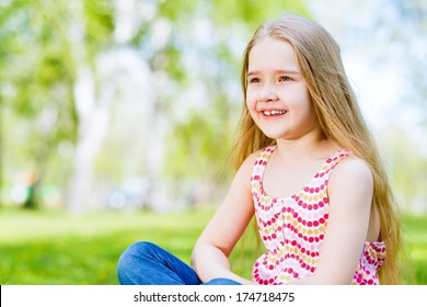 smiling girl sitting in the grass on a summer park