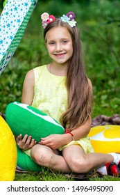 Smiling girl sitting in meadow in a tent