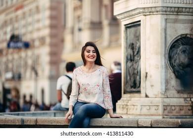 Smiling girl sitting near fountain