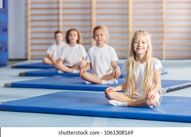 Smiling girl sitting on a blue mat during gymnastics classes