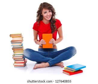 Smiling girl sitting on the floor with many colorful books, white background