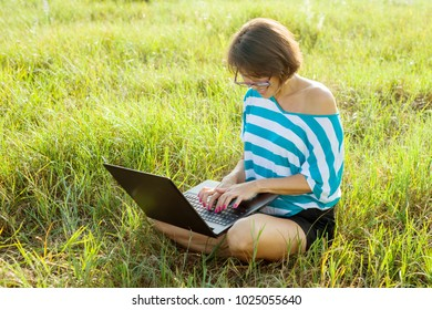 Smiling girl sitting on the grass in bright summer day and working on the computer. Using laptop outdoors, chatting with friends. Social networking and freelance.