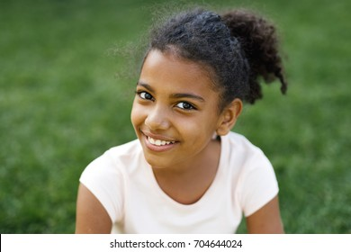 Smiling girl sitting on a grass in park, looking at camera
