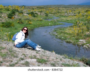 smiling girl sitting on the grass near the snake path of creek