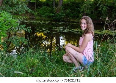 smiling girl sitting on the river bank