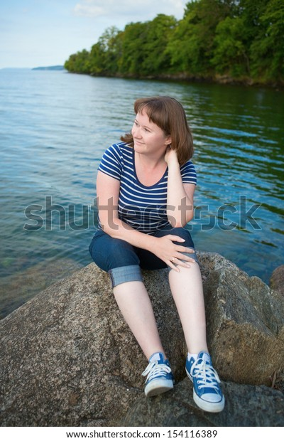 Smiling girl sitting on a rock near the lake