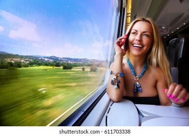 Smiling girl sitting on the train talking on the phone and looking out the window