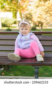 smiling girl sitting on wooden bench