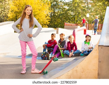Smiling girl in with skateboard and her friends
